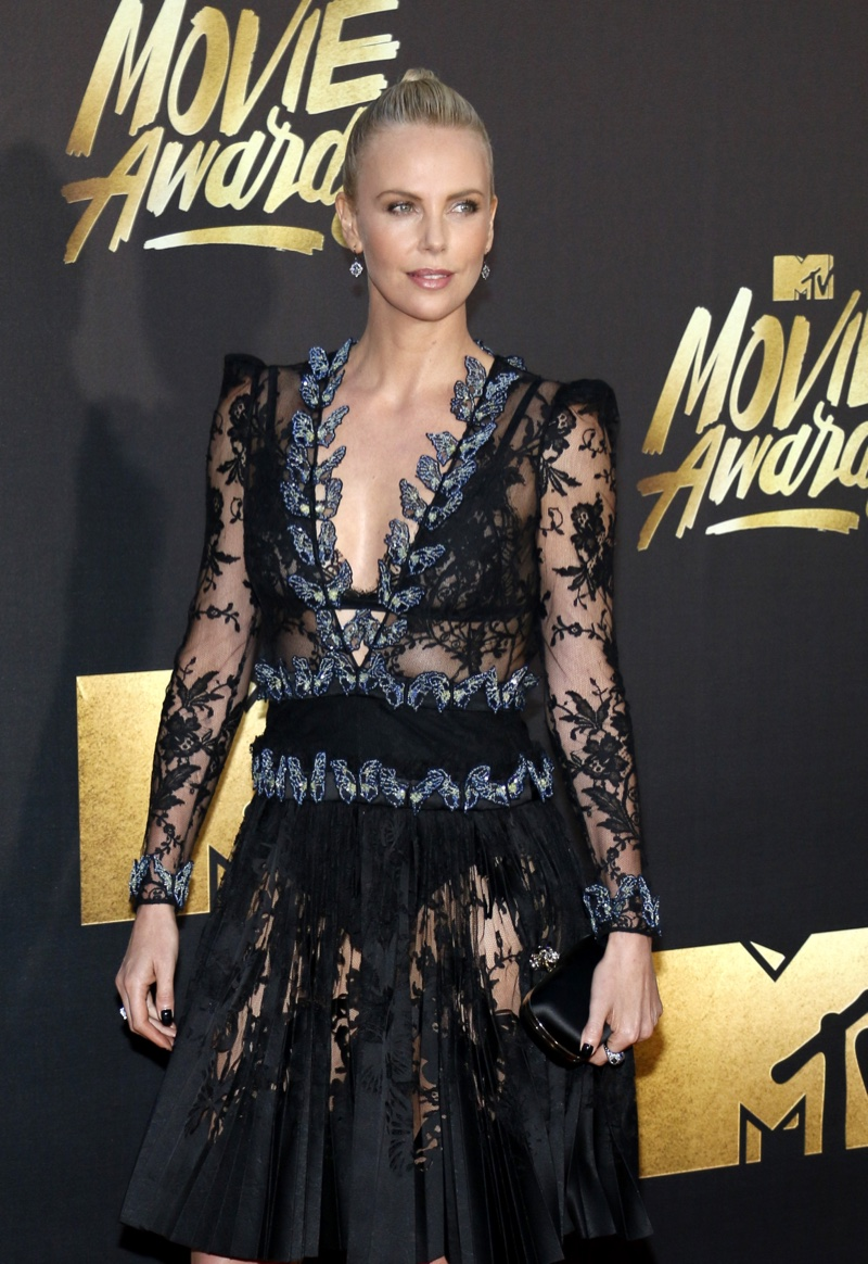 APRIL 2016: Charlize Theron attends the 2016 MTV Movie Awards wearing a black sheer lace Alexander McQueen dress. Photo: Tinseltown / Shutterstock.com