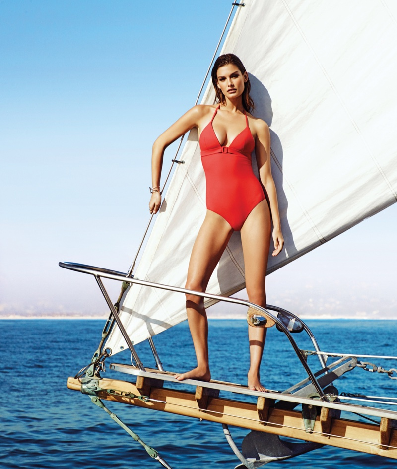 Against the backdrop of the sea, Ophelie models a one-piece swimsuit in red from Etam