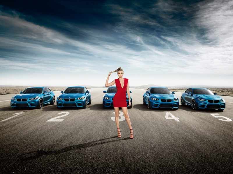 Gigi Hadid poses next to a fleet of BMW's M2 Coupé