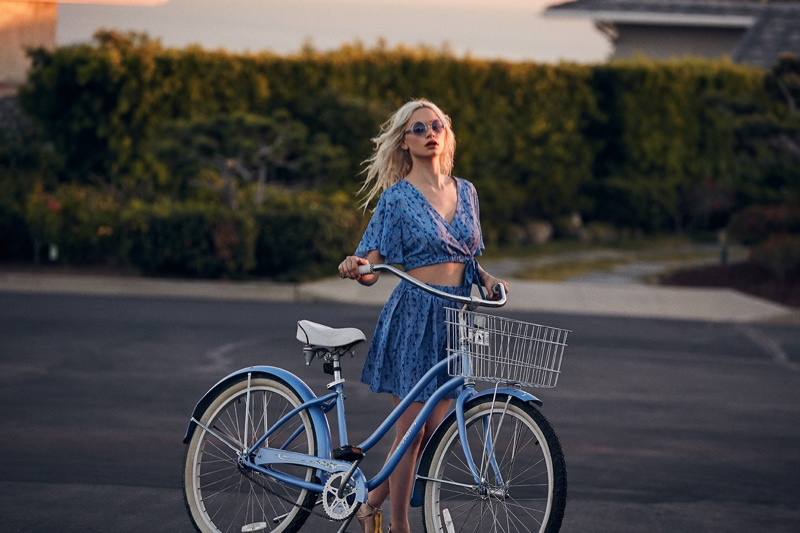 Posing with a bike, Delilah models Jack by BB Dakota Gwenifer faux wrap top and Donoma pleated skirt