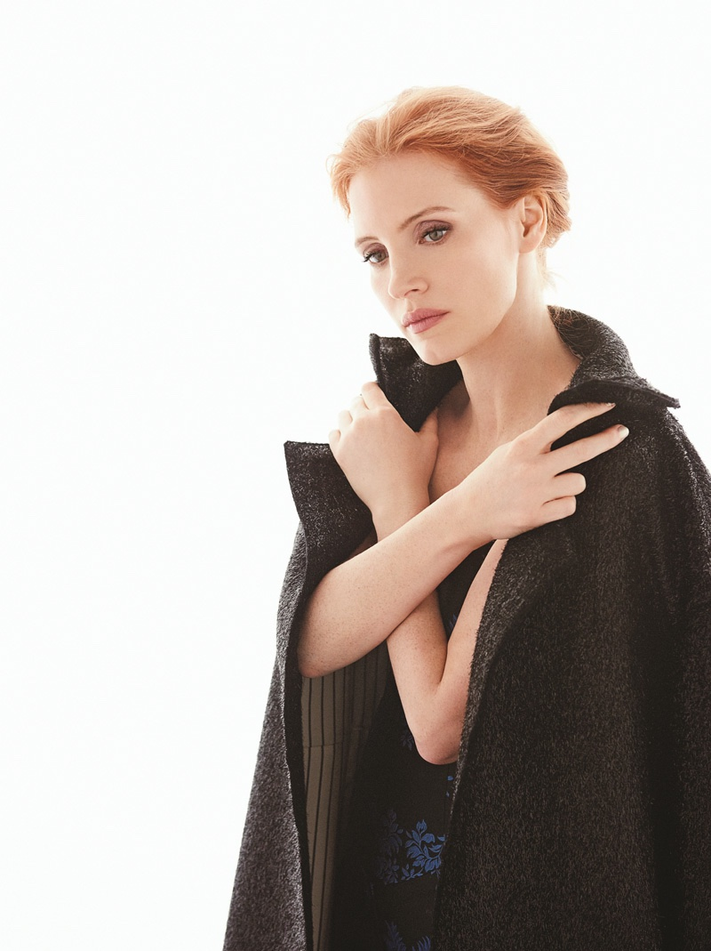 The redhead actress wears a black coat in the photo session