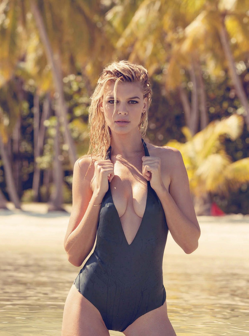 Posing on the beach, Kelly Rohrbach models a black swimsuit from Mikoh