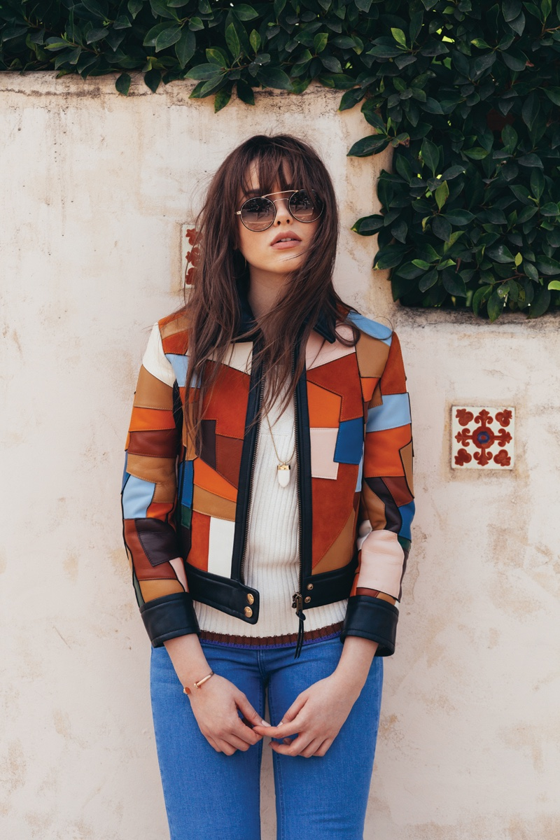 Kristina Bazan poses in a patchwork moto jacket and jeans