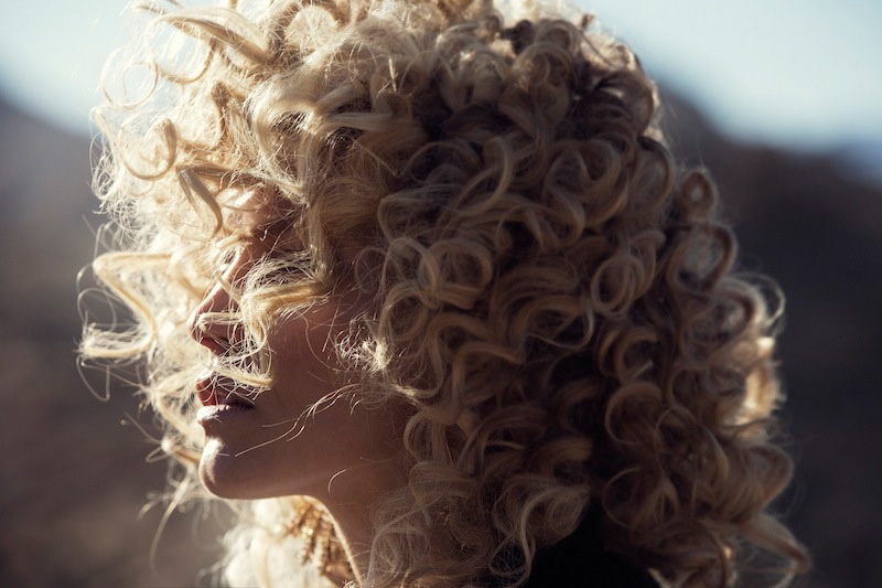 The blonde model wears a curly hairstyle