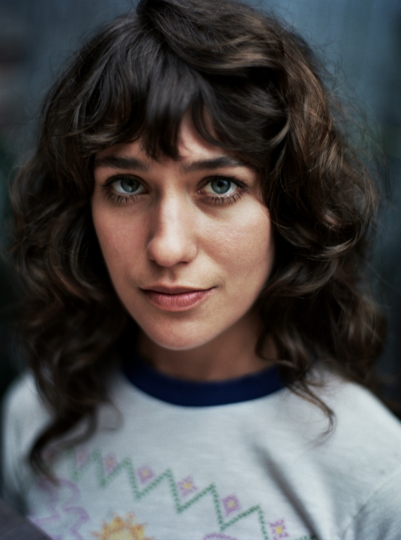 Actress Lola Kirke wears a curly hairstyle featuring long bangs