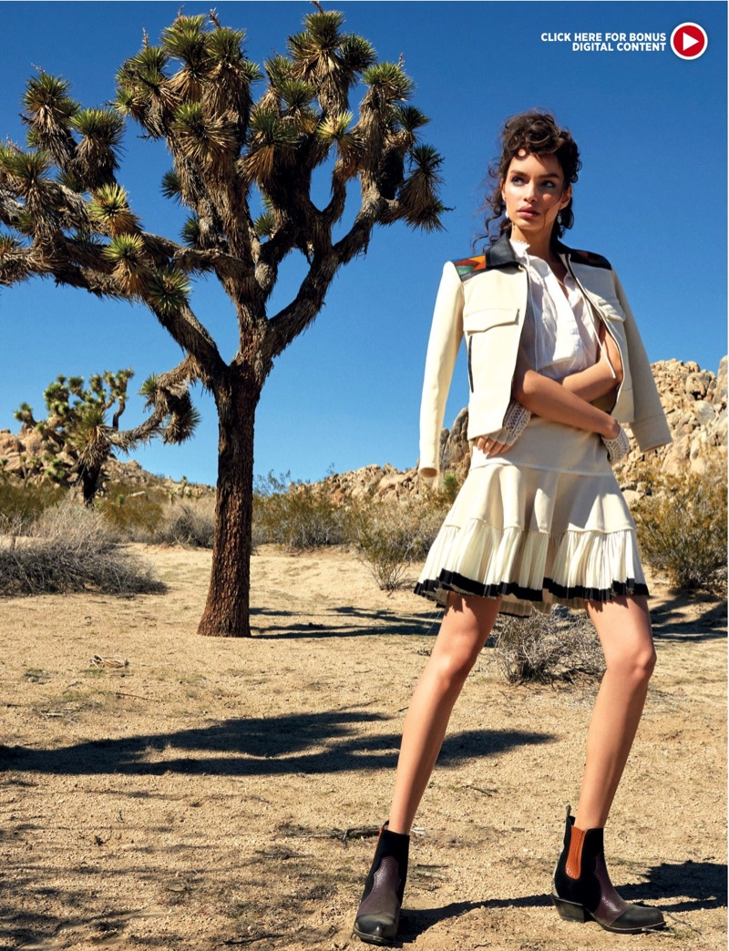The model wears a leather and cotton jacket with a white blouse a pleated skirt from Coach
