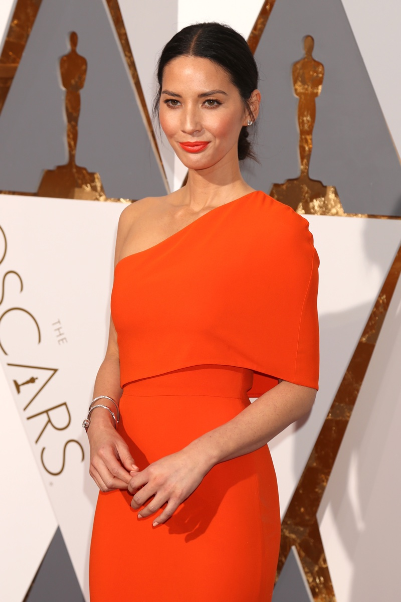 FEBRUARY 2016: Olivia Munn attends the 2016 Oscars wearing an orange Stella McCartney dress with asymmetrical draping. Photo: Helga Esteb / Shutterstock.com