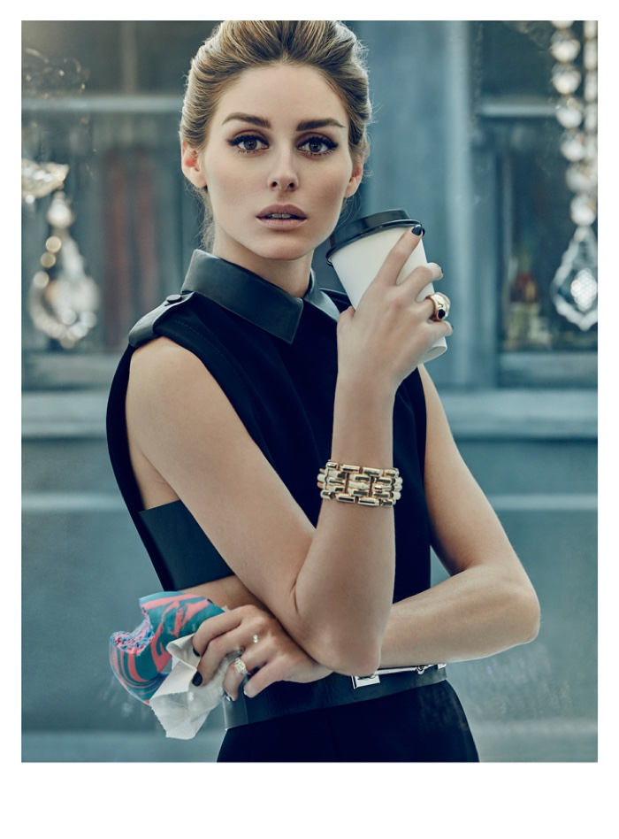Holding a coffee cup and bagel, Olivia Palermo wears a black dress