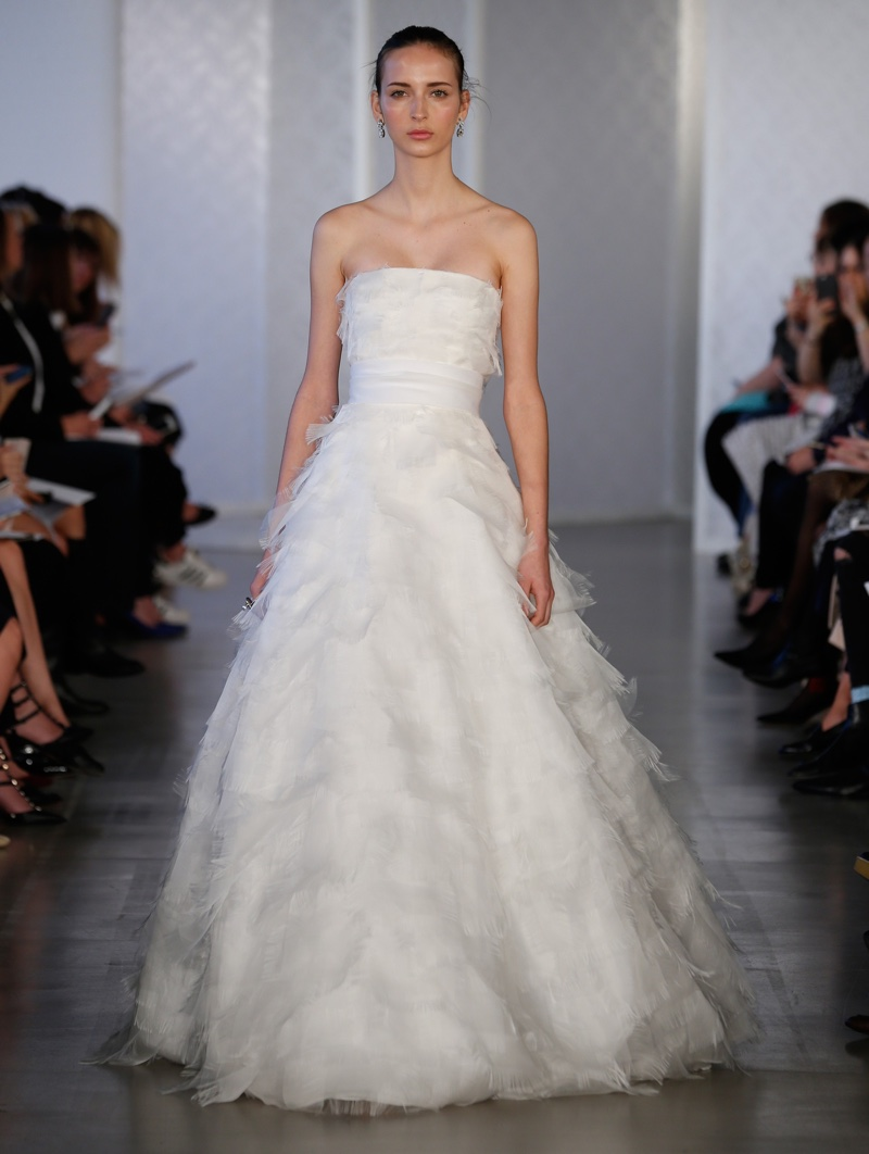 A model walks the runway at Oscar de la Renta Bridal's spring 2017 show wearing a strapless gown with layered organza