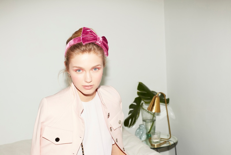 Romy wears a headband with a pink bow and pastel-colored jacket