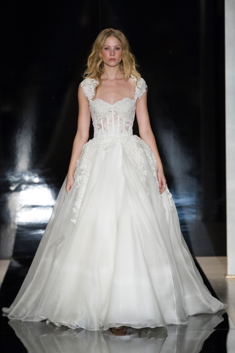 A model walks the runway at Reem Acra's spring 2017 bridal show wearing an organza layered ball gown with embroidered bodice