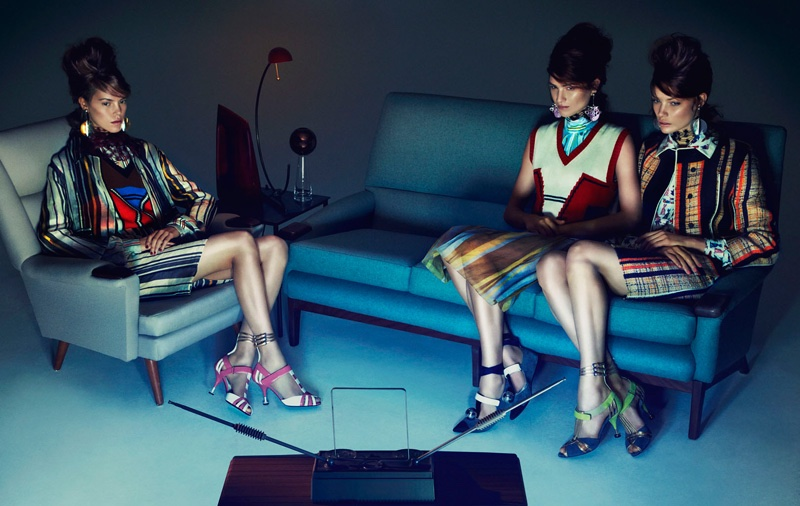 The models pose on couches, looking mod cool in Prada ensembles with mini skirts and sweater vests