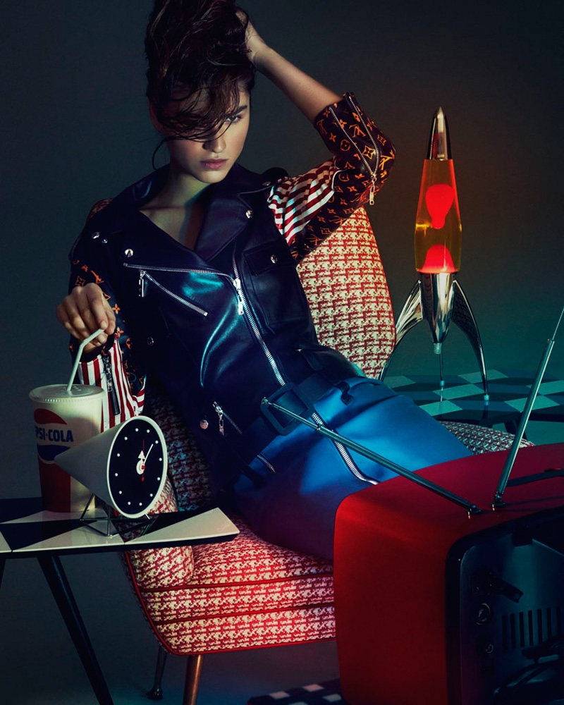 Channeling retro style, model wears Louis Vuitton leather coat with striped and LV monogram sleeves
