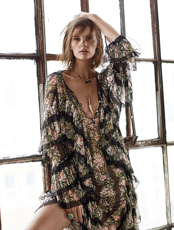Posing next to a window, Sara Blomqvist models a Gucci floral print dress with ruffles