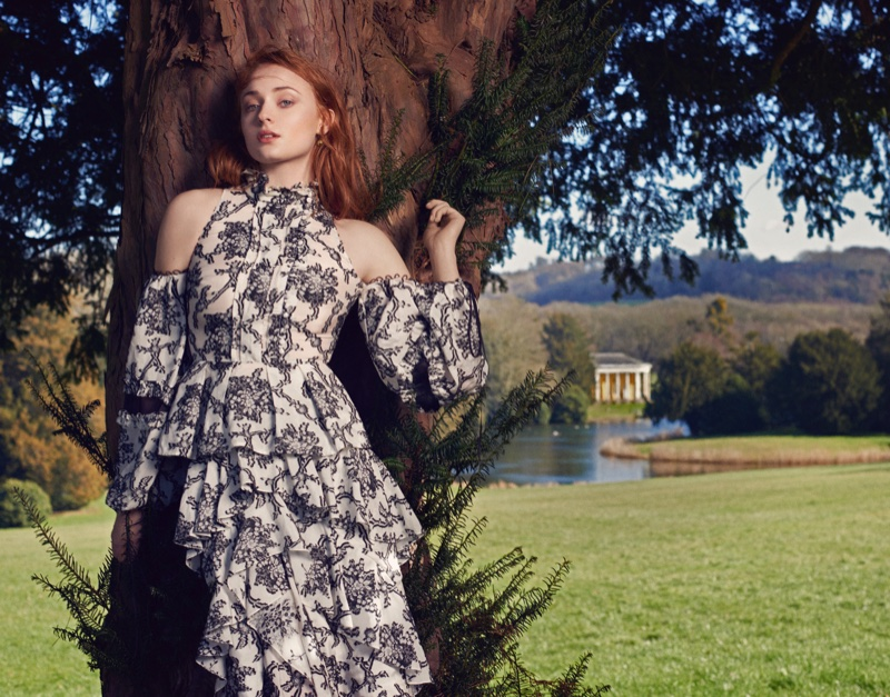 Sophie Turner poses in an Erdem top with open shoulder and matching skirt featuring ruffles