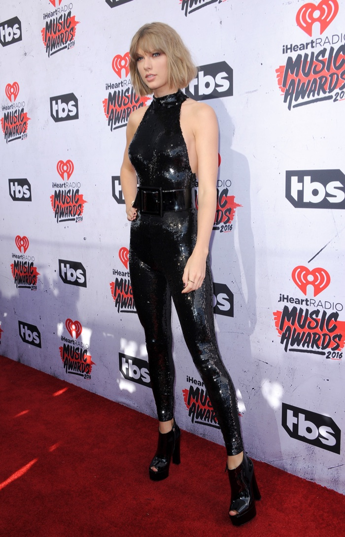 APRIL 2016: Taylor Swift attends the 2016 iHeart Radio Awards wearing a black Saint Laurent jumpsuit with sequin embellishment. Photo: Tinseltown / Shutterstock.com