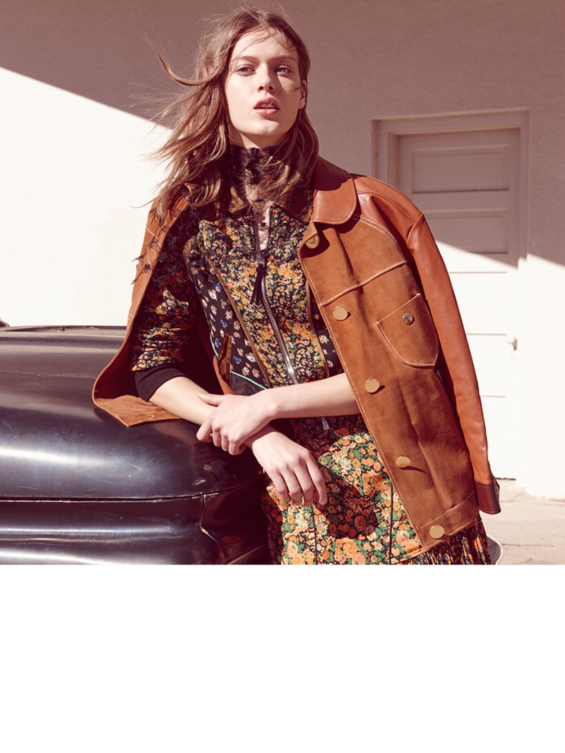 Posing next to a car, the model wears a brown jacket layered over a floral print dress