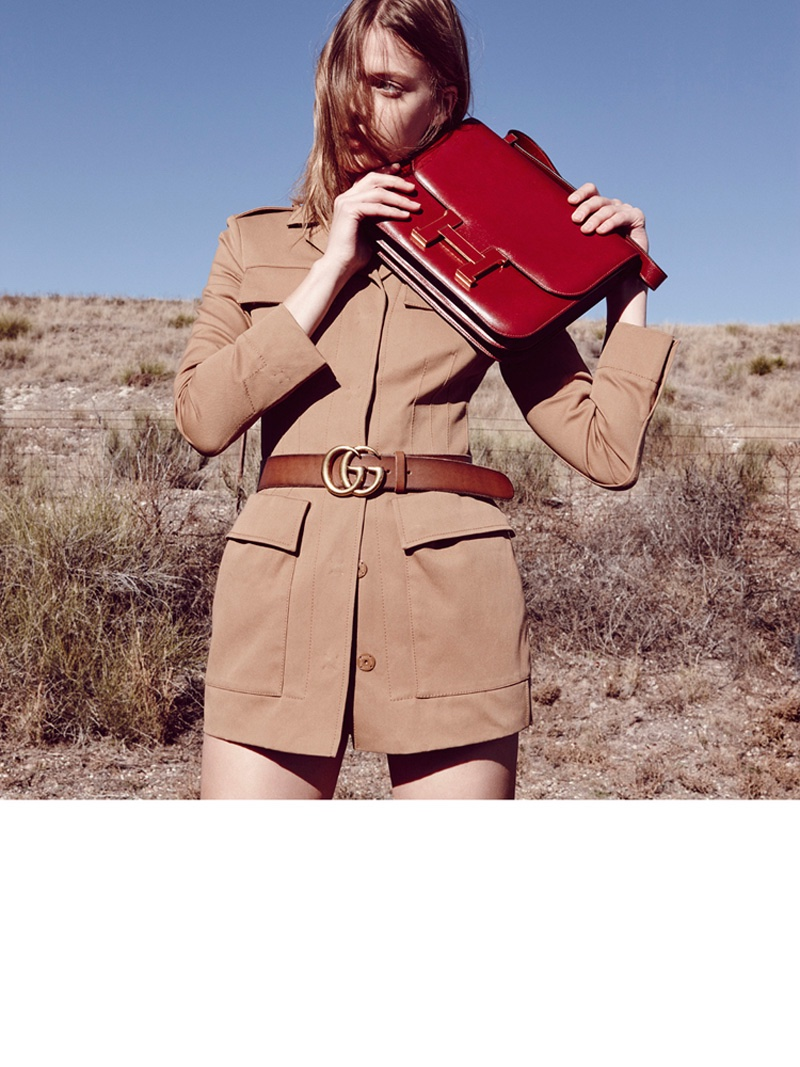 Tess poses in a brown jacket featuring a Gucci belt and oversized red Hermes clutch