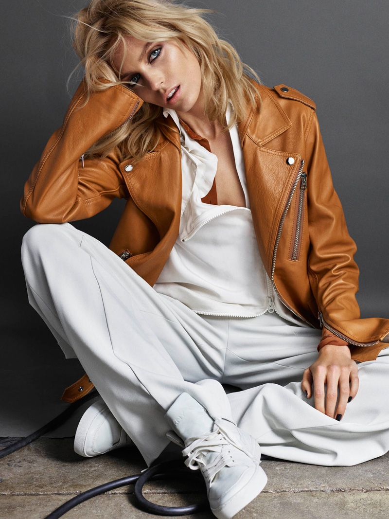 Anja Rubik wears a brown leather jacket, white shirt and pants