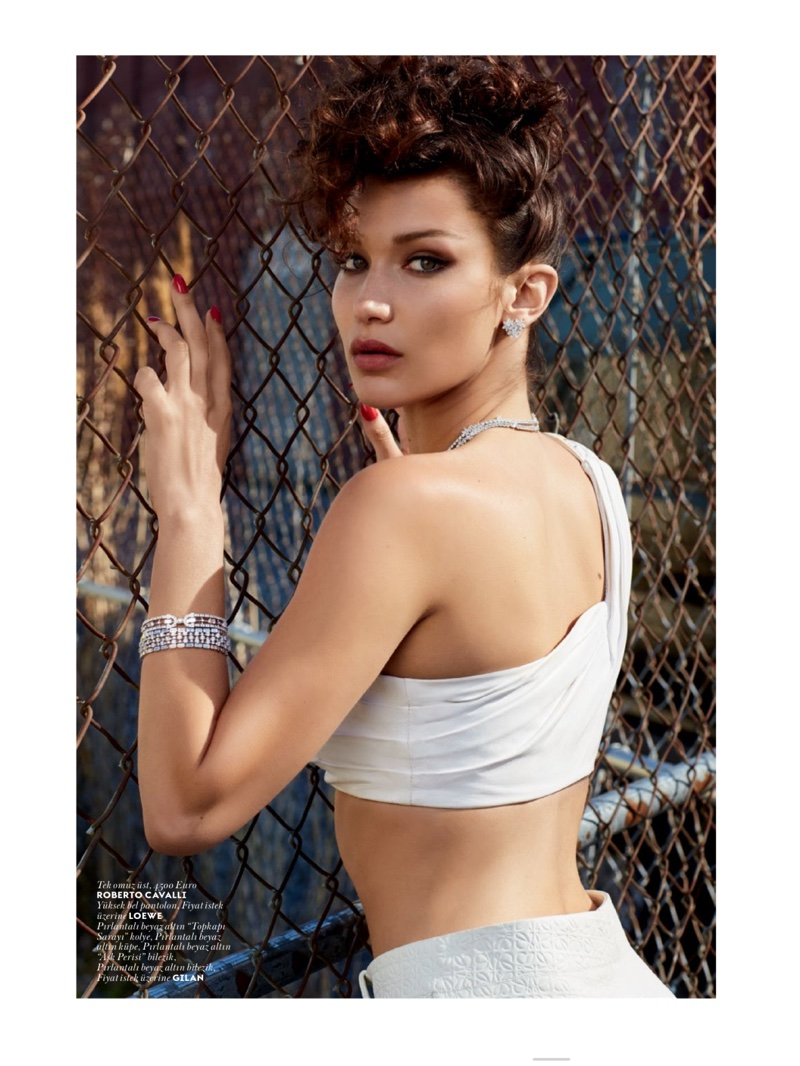 Gazing into the camera's lens, Bella Hadid wears Roberto Cavalli top, Loewe bottoms and jewelry by Gilan