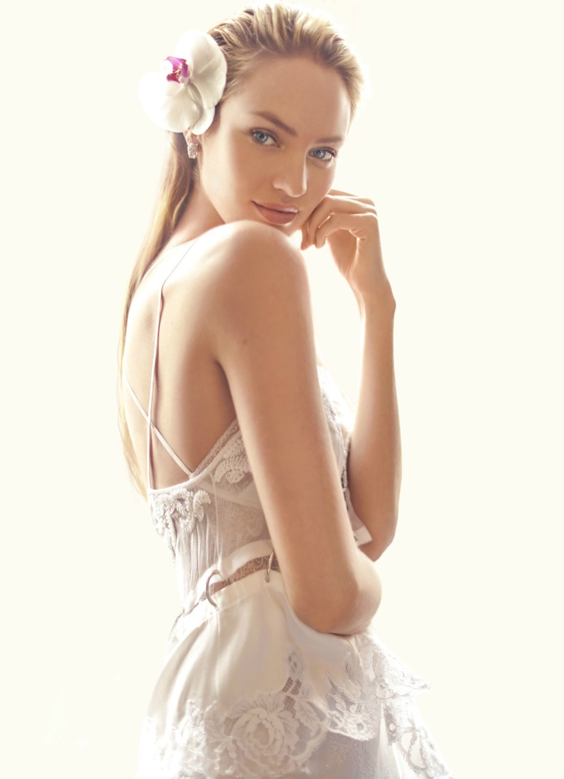 Candice Swanepoel models a white Givenchy lace top with a flower in her hair