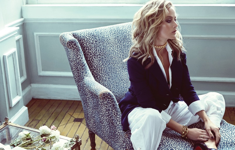 Sitting in a chair, the model wears a Ralph Lauren blazer, shirt and wide-leg trousers