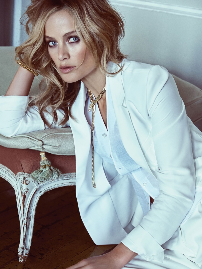 The model suits up in an all white look featuring a suit jacket and shirting