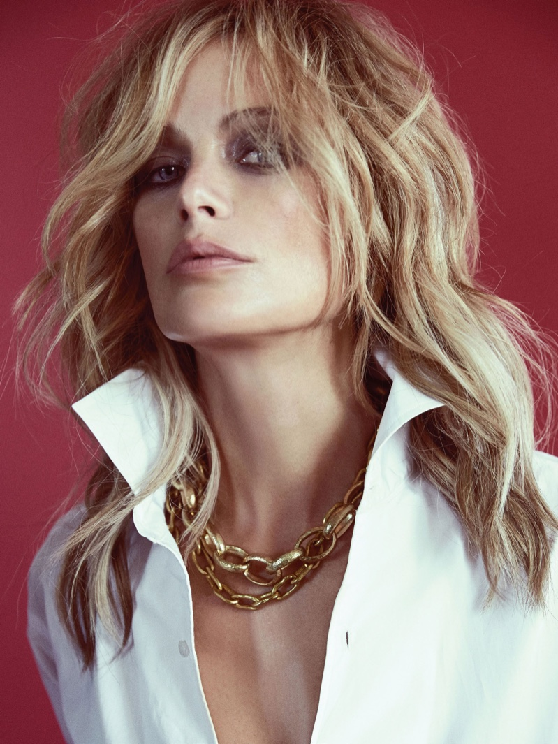 Wearing a wavy hairstyle, Carolyn Murphy poses with gold chain necklace and button-up top