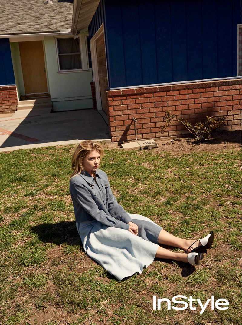 Posing on grass, Chloe Grace Moretz wears blue jacket and skirt look