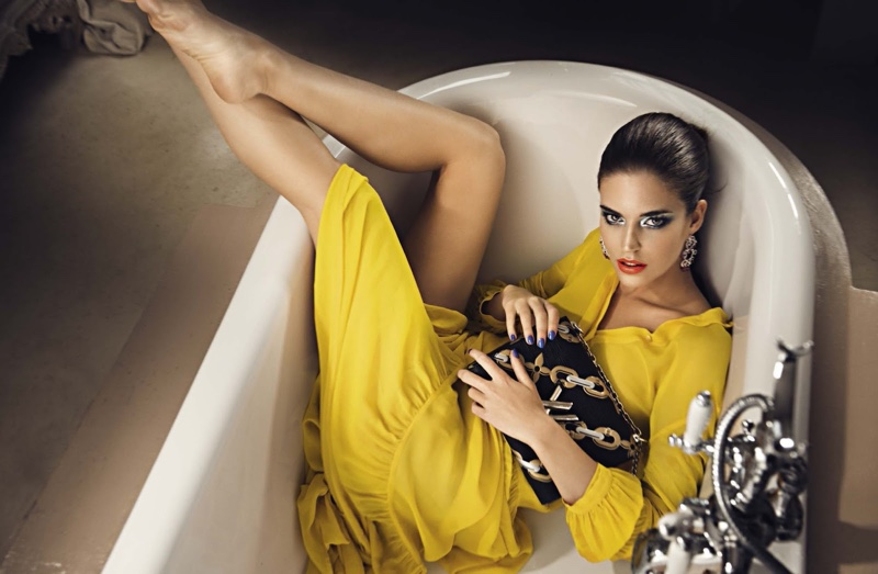 Clutching on to a Louis Vuitton bag, Clara poses in a tub