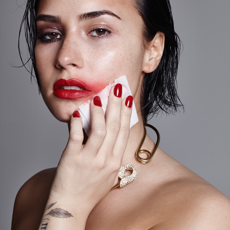 Demi Lovato wears a bold red lipstick with a matching manicure