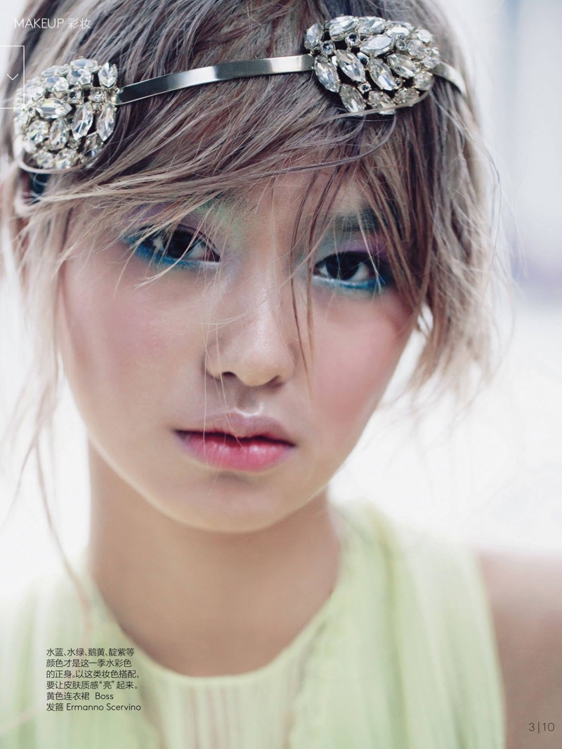 Wearing a crystal embellished headband, Estelle wears pastel colored  eyeshadow with pink-blush on her cheeks