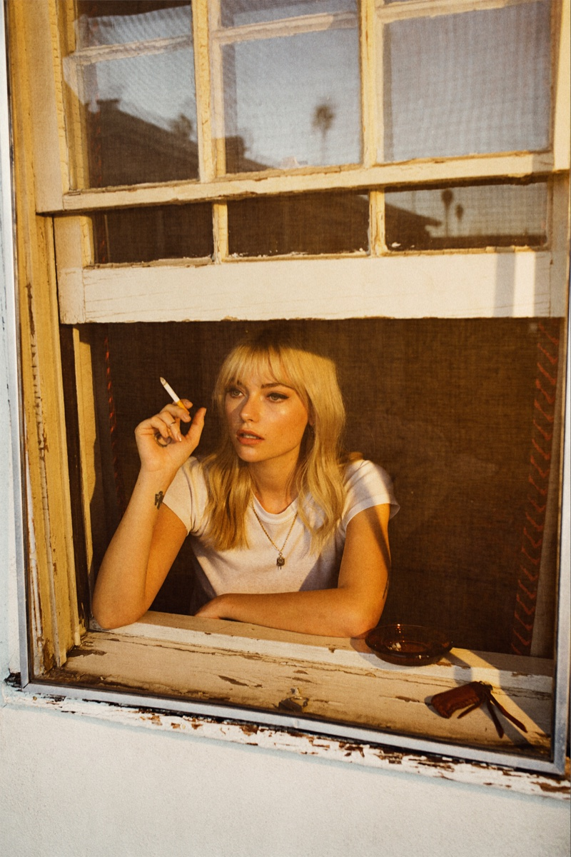 Holding a cigarette in hand, Farah Holt poses in a white t-shirt