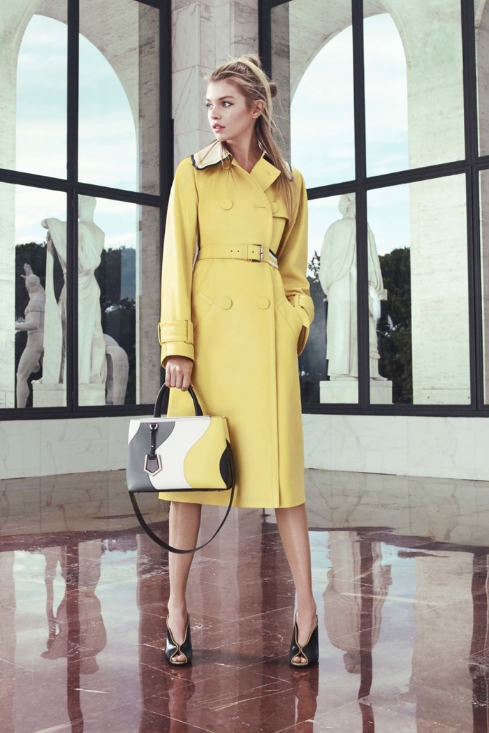 A look from Fendi's resort 2017 collection featuring a yellow trench coat