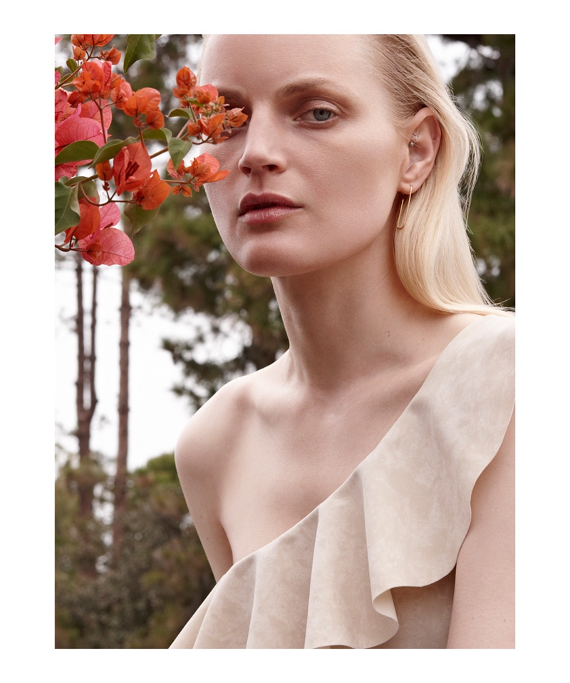 Guinevere van Seenus poses with flowers while wearing one shoulder ruffle embellished top