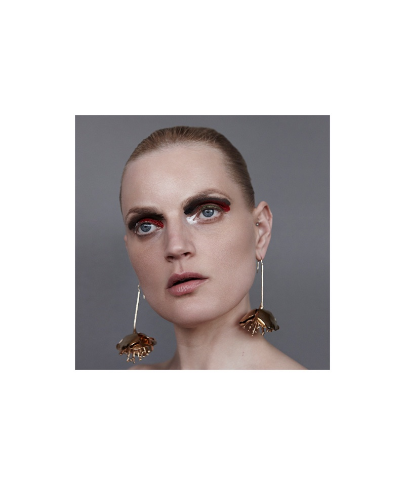 The model wears a dangling set of earrings