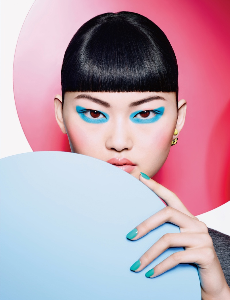 He Cong wears a bold blue eye makeup look with a teal-colored manicure
