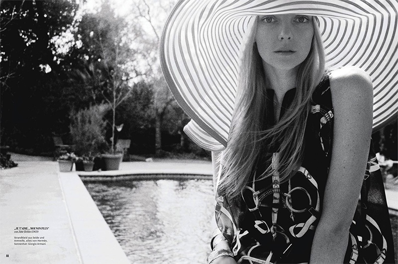 Photographed in black and white, Heather Marks models Hermes printed beach dress with Giorgio Armani hat
