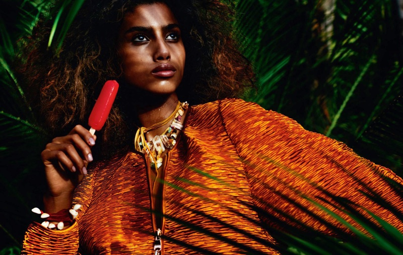 With a popsicle in hand, Imaan Hammam models zip-up top with embellished necklace and bracelet