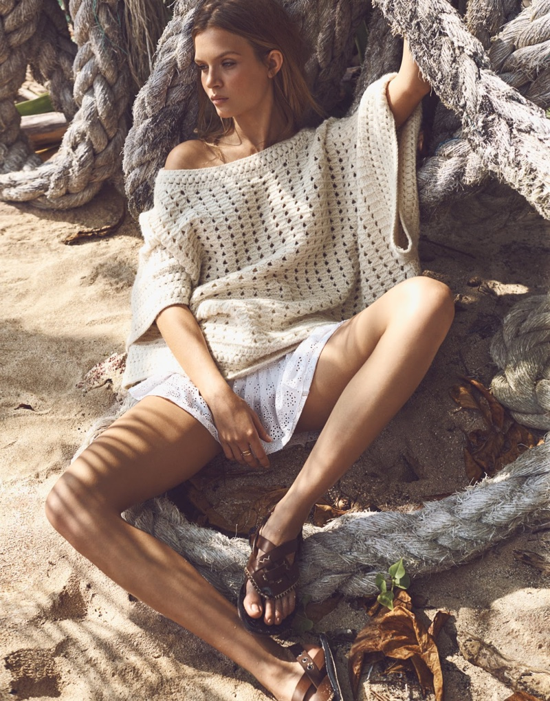 Josephine Skriver lounges on the sand wearing a Chloe Cape, LoveShackFancy Skirt and Bottega Veneta sandals