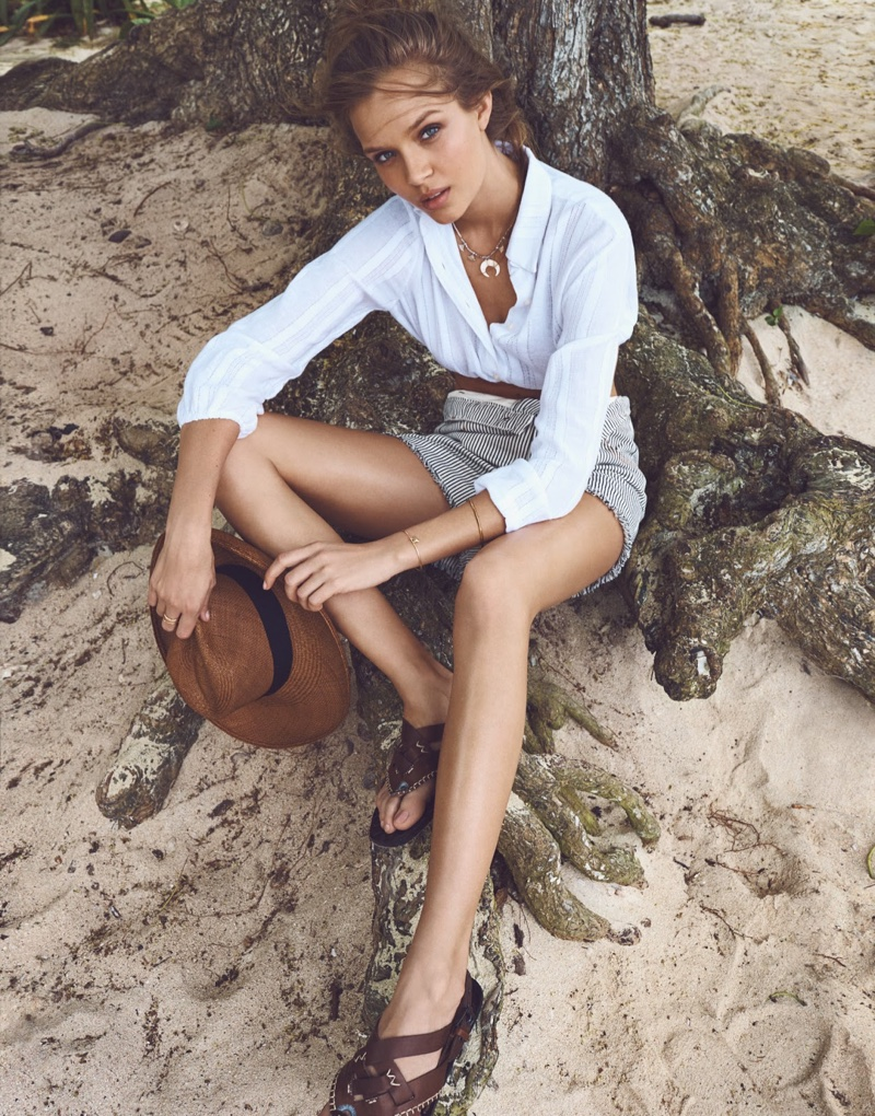 The model is captured wearing a white blouse and shorts