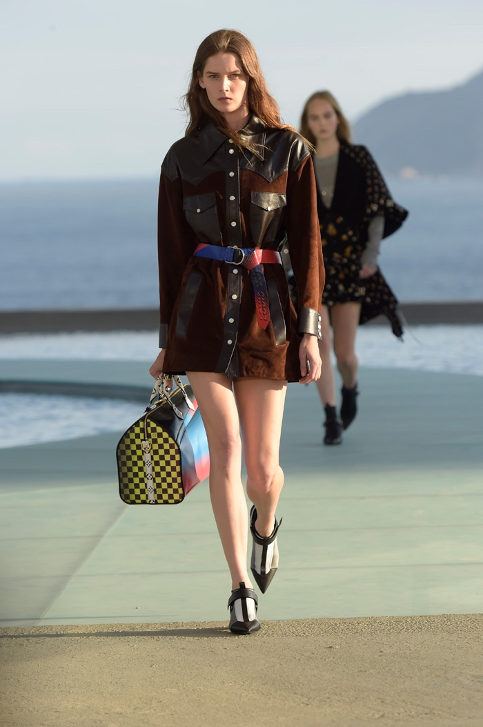 A model walks the runway at Louis Vuitton's resort 2017 show wearing a belted jacket