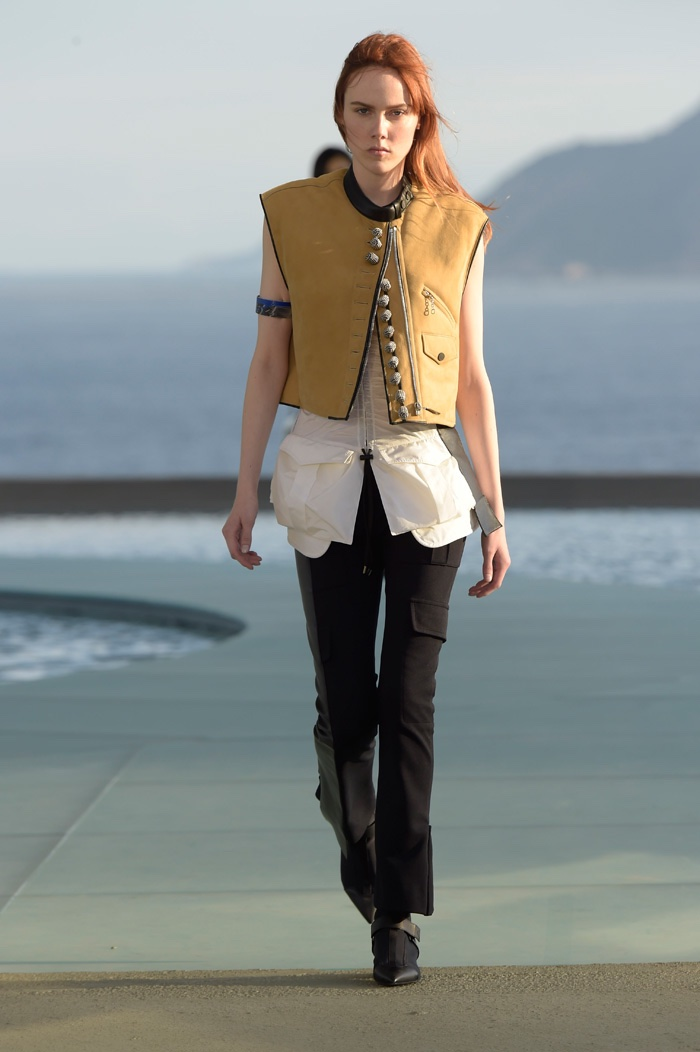 A model walks the runway at Louis Vuitton's resort 2017 show wearing a cropped vest, long blouse and fitted trousers
