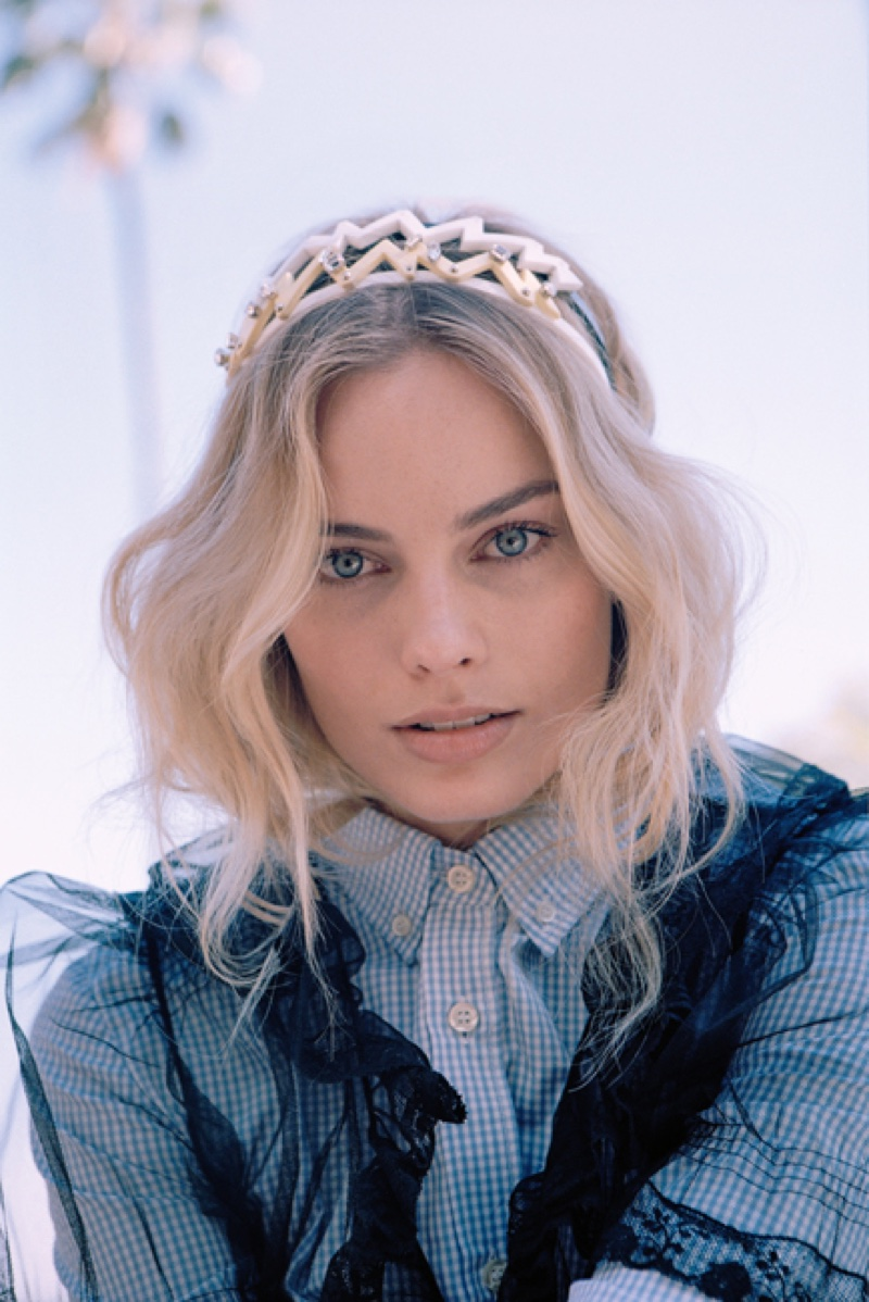 With her blonde hair in carefree waves, Margot Robbie wears Miu Miu shirt, dress and embellished headbands