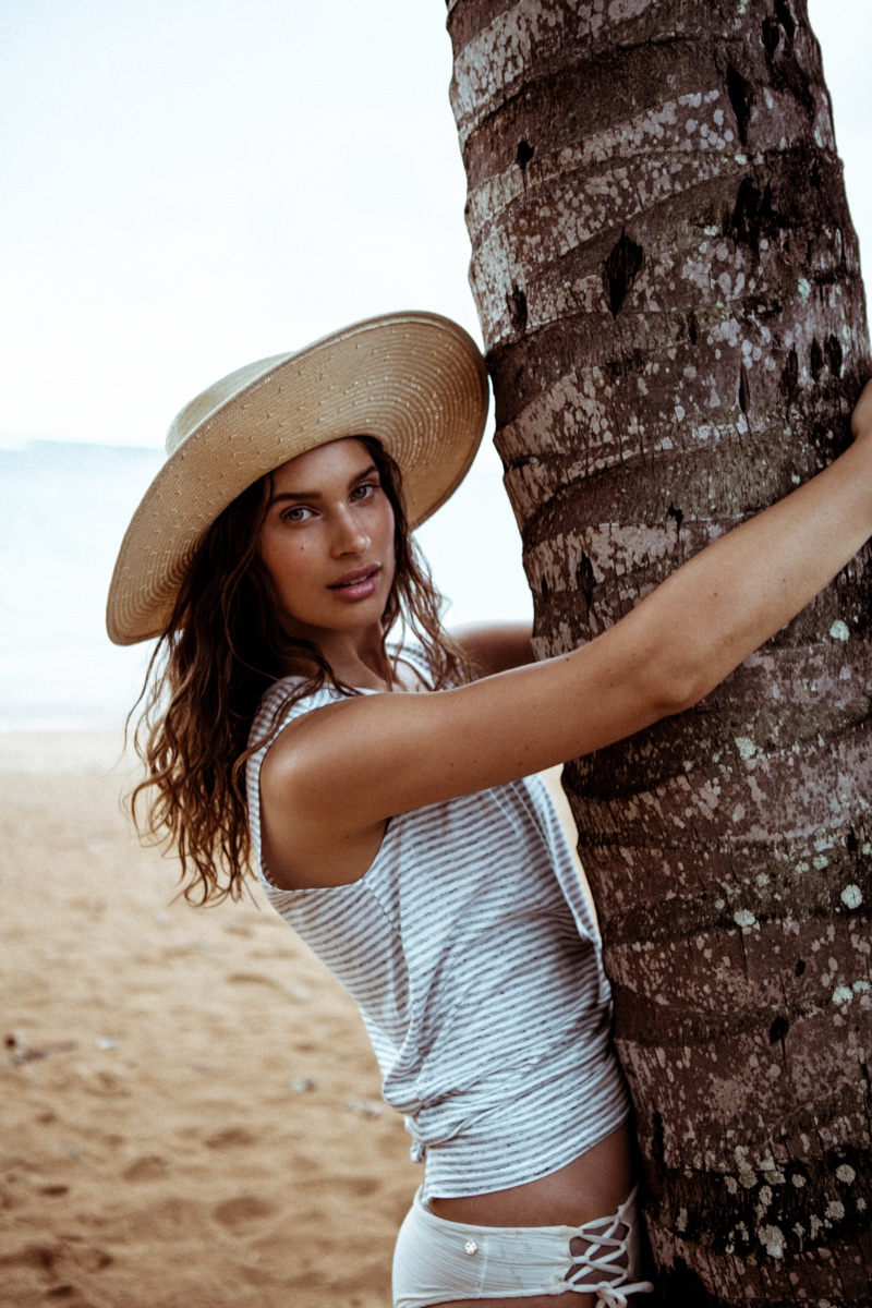 Wearing a sun hat, Lise Bjørgen Olsen poses in a Mate the Label tank top