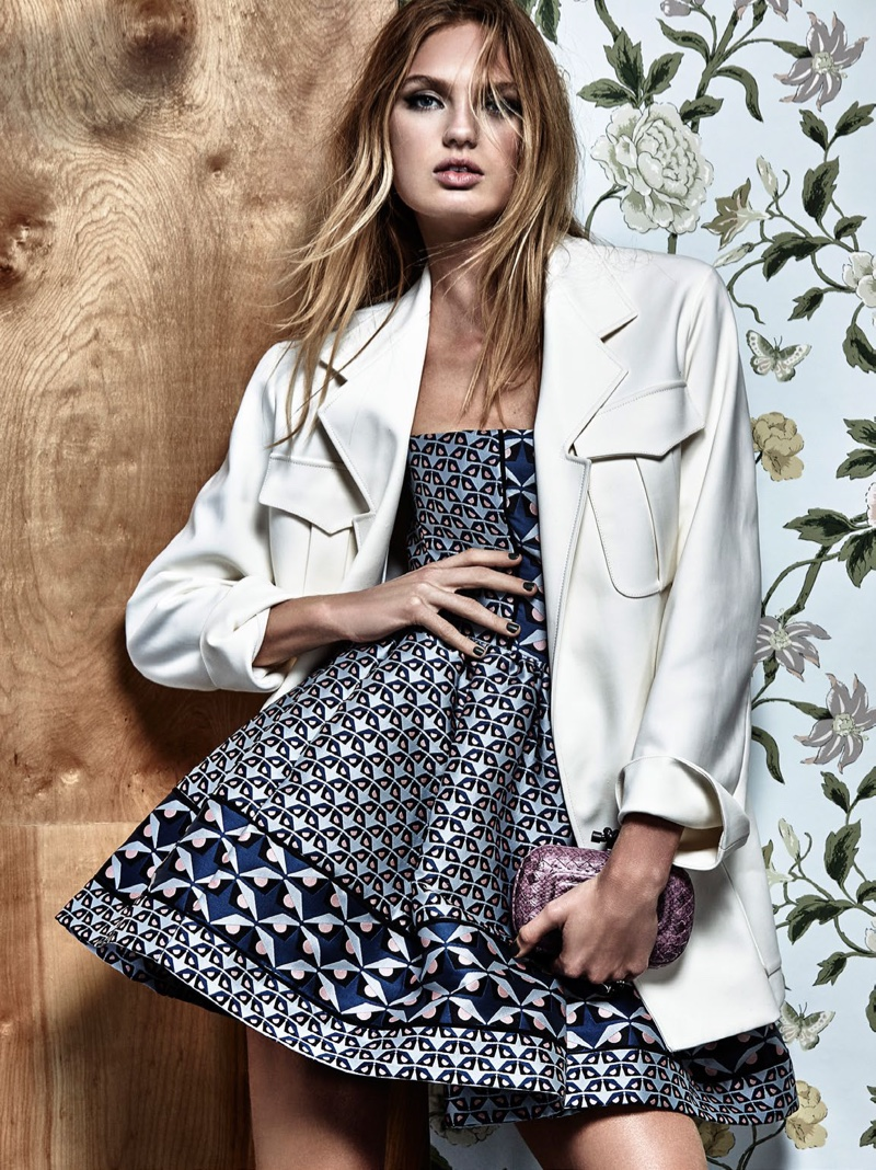 Romee Strijd wears a white trucker jacket with fit and flare dress