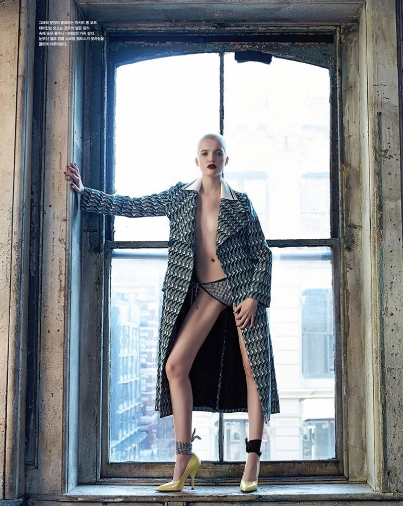 Clad in a Miu Miu coat and heels, Ruth Bell poses in front of an open window