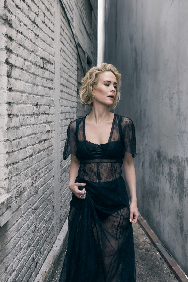 Sarah Paulson wears a black sheer lace dress with bra and underwear