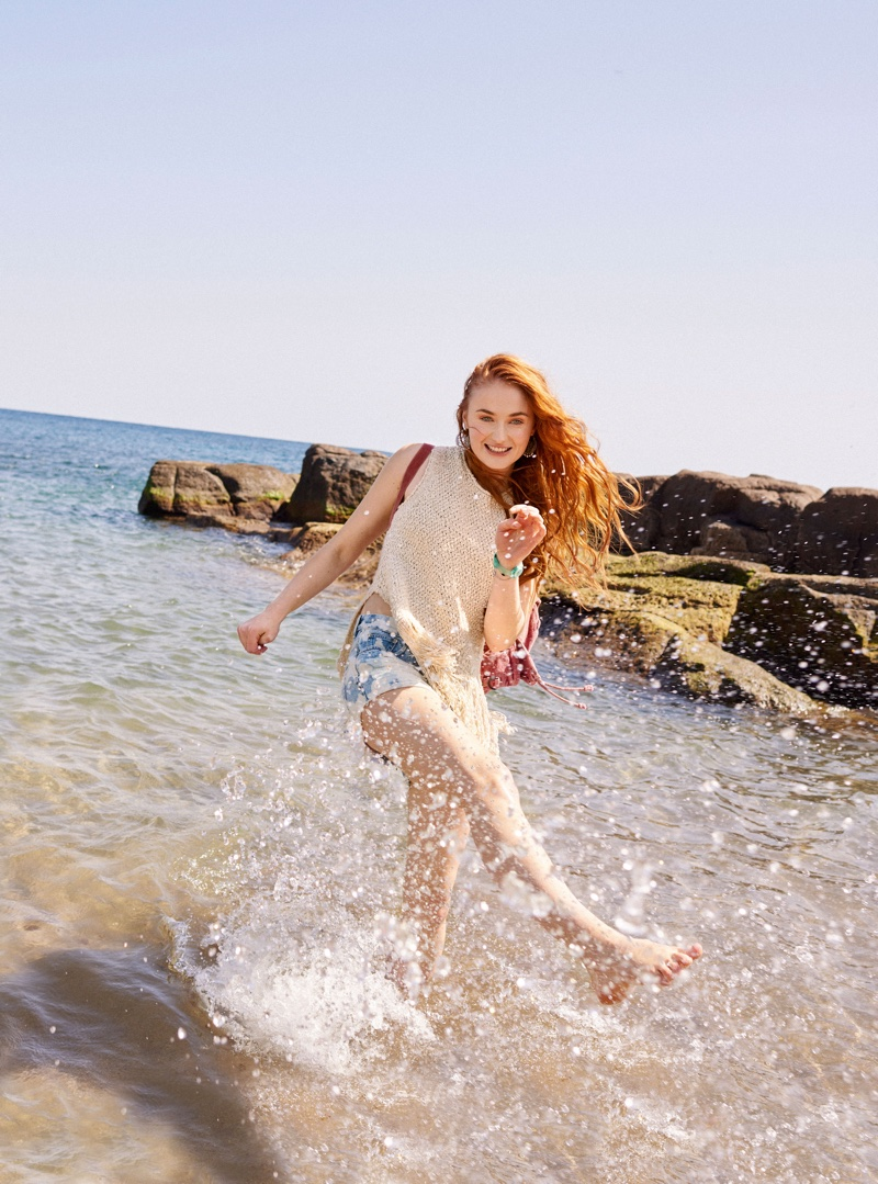 Sophie Turner heads to the beach in long tunic and denim shorts