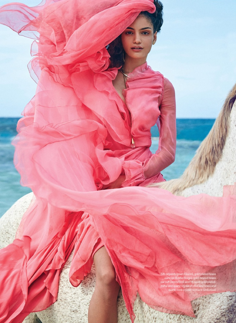The model takes to the beach in a pink Gucci gown with ruffles